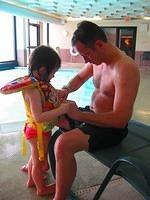 This isn't NASCAR, but to Scott & Cami's kids, it's even better... it's swimming!  Scott helps Morgan into her life jacket a